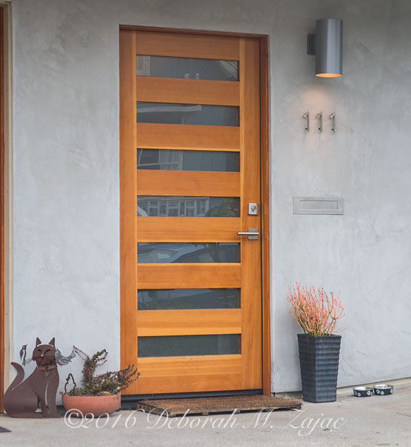 Front door with cat decoration and pots